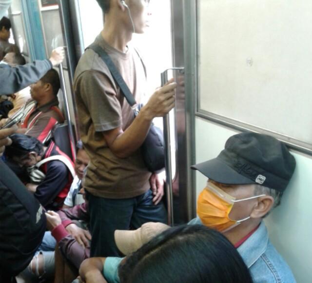 Penumpang duduk di lantai Commuter Line